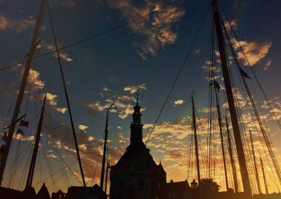 De hoofdtoren van Hoorn omgeven door de prachtige masten van traditionele zeilcharterschepen
